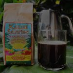 This is an image of a bag of Kauai Sunrise coffee on a table with a cup of coffee and french press