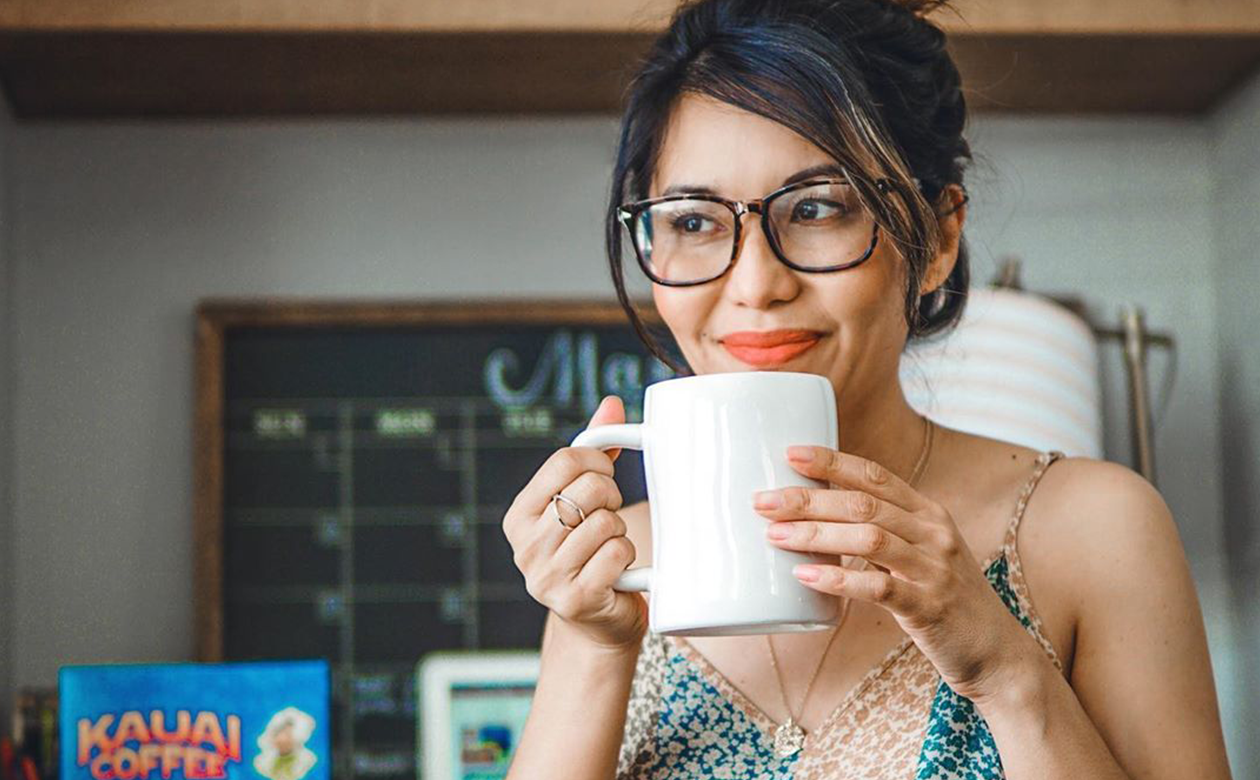 young woman drinking Kauai coffee from a white porcelain mug. There is a calendar and home office space in the background