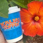 blue kauai coffee to go cup and a bright red hibiscus flower